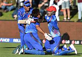 Afghanistan batsman Shapoor Zadran celebrates with teammate Hamid Hassan after hitting the winning runs to defeat Scotland as reserve Usman Ghani...
