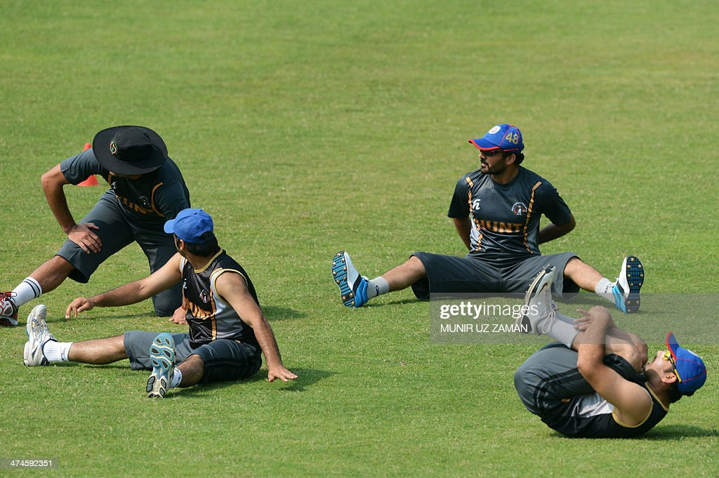 Afghanistan cricketer Nawroz Mangal (2R) stretches with his teammates during a team training session at the Sher-e-Bangla National Cricket Stadium in Dhaka on February 24, 2014. AFP PHOTO/Munir uz ZAMAN