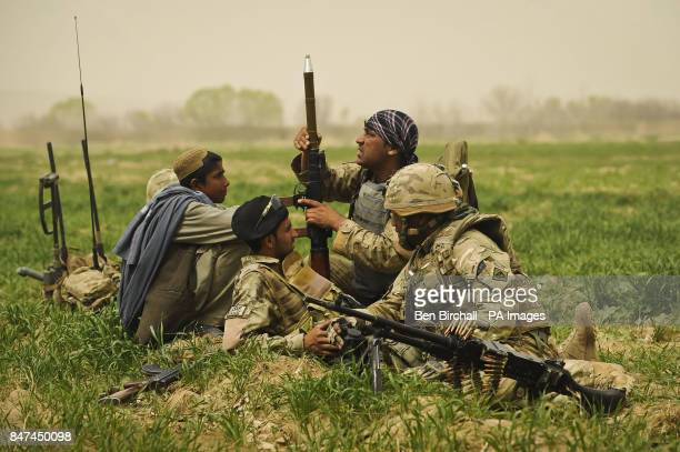Afghanistan National Order Civil Police British forces personnel and Afghan locals rest in a field as they inspect a Rocket Propelled Grenade...