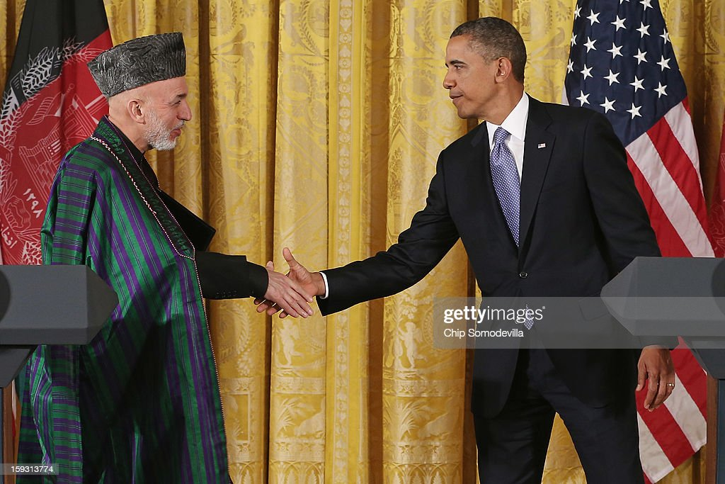 Afghanistan President <a gi-track='captionPersonalityLinkClicked' href=/galleries/search?phrase=Hamid+Karzai&family=editorial&specificpeople=121540 ng-click='$event.stopPropagation()'>Hamid Karzai</a> (L) and U.S. President <a gi-track='captionPersonalityLinkClicked' href=/galleries/search?phrase=Barack+Obama&family=editorial&specificpeople=203260 ng-click='$event.stopPropagation()'>Barack Obama</a> shake hands after a joint news conference in the East Room of the White House January 11, 2013 in Washington, DC. Karzai is in Washington for face-to-face meetings with Obama and senior members of his administration about the future of American commitment to Afghanistan and when troops may leave the country after more than 10 years of war.