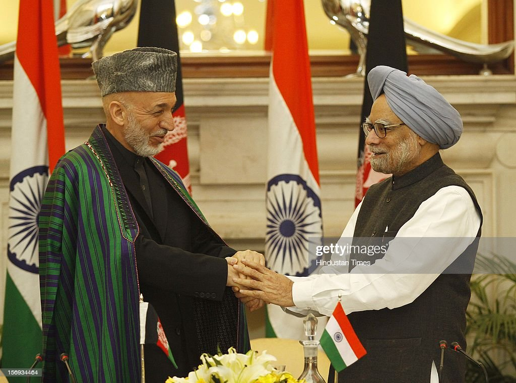 Afghanistan President Hamid Karzai (L) shakes hand with Prime Minister Manmohan Singh after the delegation level talks and an agreement signing ceremony at Hyderabad House in New Delhi on November 12, 2012 in New Delhi, India.