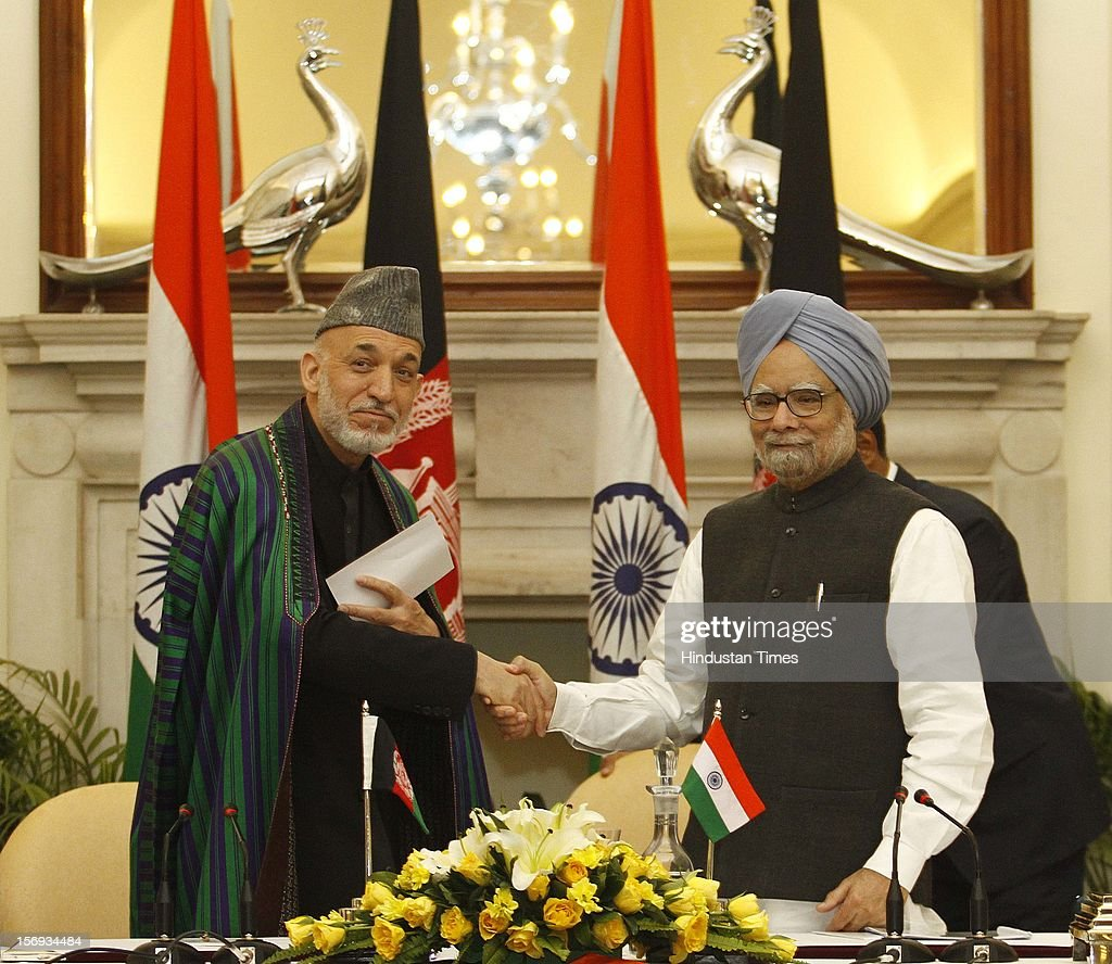 Afghanistan President Hamid Karzai (L) shakes hand with Prime Minister Manmohan Singh after the delegation level talks and an agreement signing ceremony at Hyderabad House on November 12, 2012 in New Delhi, India.