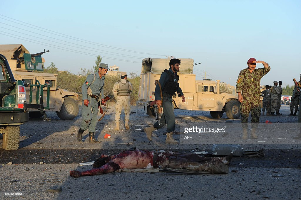 Afghanistan security forces walk past a dead body during an attack on the US consulate in Herat on September 13, 2013. Gunmen staged an attack on the US consulate in Herat, western Afghanistan leaving at least one person dead and 18 wounded, officials said. Four policemen were among the wounded, Herat hospital spokesman Mohammad Rafiq Sherzai said.