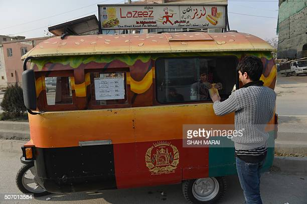 AfghanistanlifestylefoodFEATURE In this photograph taken on December 27 an Afghan customer buys a burger from a Lazeez food truck in Kabul When the...