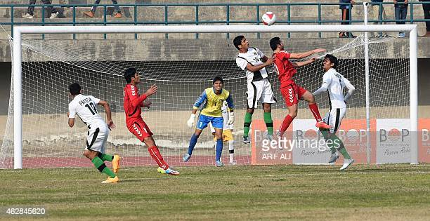 Afghanistan's Balal Arezou vies the ball with Pakistan's Mohsin Ali during their friendly football match at the Punjab stadium in Lahore on February...