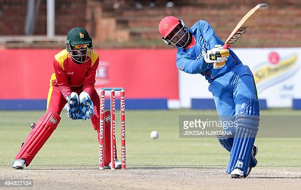 Afghanistan's batsman batsman Usman Ghani plays a shot as Richmond Mutumbami looks on during the first game in a series of two T20 cricket matches...