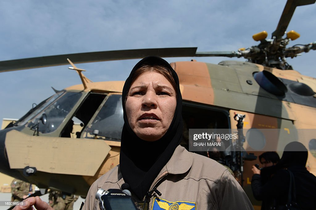 Afghanistan's first female pilot, Latifa Nabizada ,40, gives an interview as she stands next to a helicopter at the Kabul International Airport (KAIA), in Kabul on March 7, 2013, on the eve of Inte...