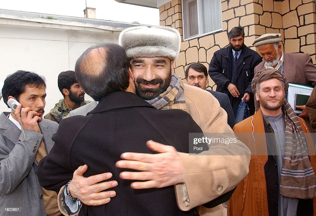 Afghanistan's Minister of Refugees and Repatriation Inayatullah Nazeri (L) and Atta Mohammad, hug following their meeting at the Ministry of Foreign Affairs February 28, 2003 in Mazar e Sharif, Afghanistan. The two were part of a group, which included General Abdul Rashid Dostum and other factional leaders from northern Afghanistan, which unanimously agreed to improve the infrastructure of the region so that displaced people can return home. Ustad Sayeedi, leader of the Hezb-i-Wahdat party, looks on (R).