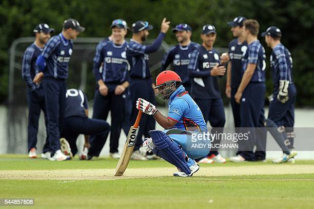 Afghanistan's Mohammad Shahzad reacts as Scotland players celebrate during play in the 1st One Day International between Scotland and Afghanistan at...