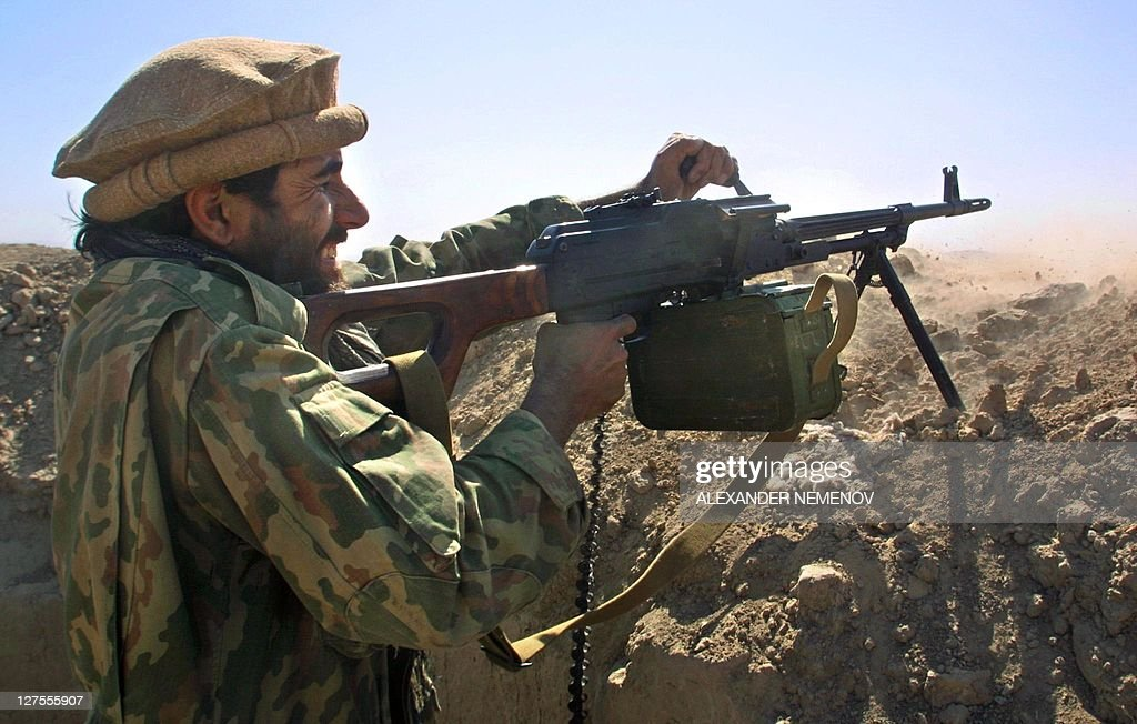Afghanistan's Northern Alliance soldier fires his Kalashnikov machinegun at his position on the front line 700 meters from Talibans 14 October 2001...
