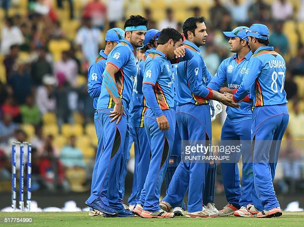Afghanistan's players gather as they celebrate after the wicket of West Indies's batsman Dwayne Bravo during the World T20 cricket tournament match...