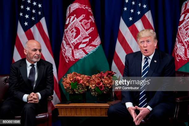 Afghanistan's President Ashraf Ghani listens while US President Donald Trump makes a statement for the press before a meeting at the Palace Hotel...