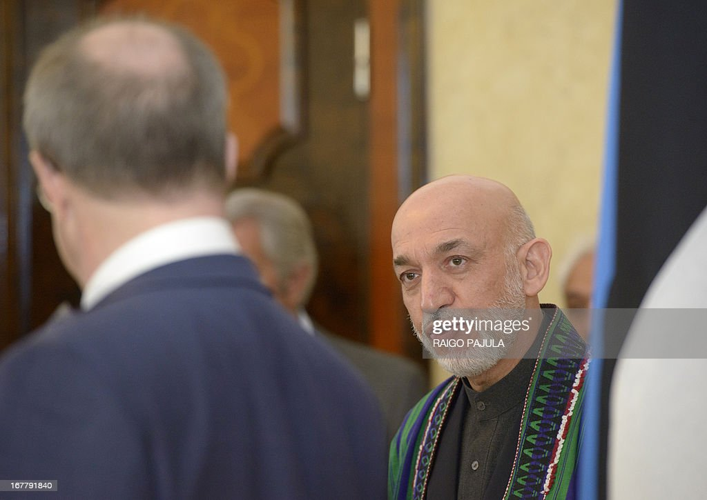 Afghanistan's President Hamid Karzai (R) and Estonian President Toomas Hendrik Ilves (L) talk during a meeting in Tallinn, Estonia on April 30, 2013. Karzai arrived on Monday, April 29, 2013 for a two day official visit to the Baltic state. AFP PHOTO / RAIGO PAJULA