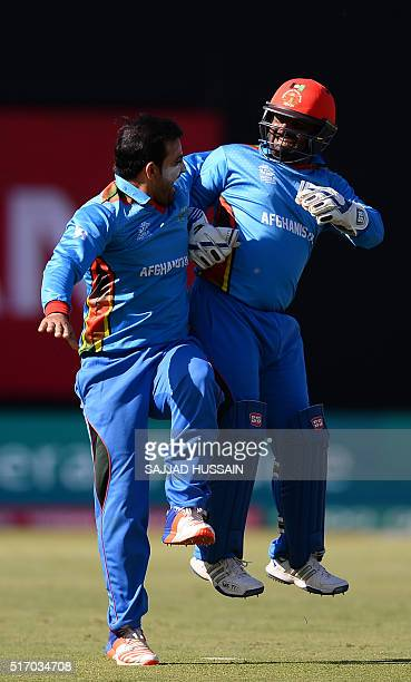 Afghanistan's Rashid Khanand teammate Mohammad Shahzad celebrate the dismissel of England's batsman Joe Root during the World T20 cricket tournament...
