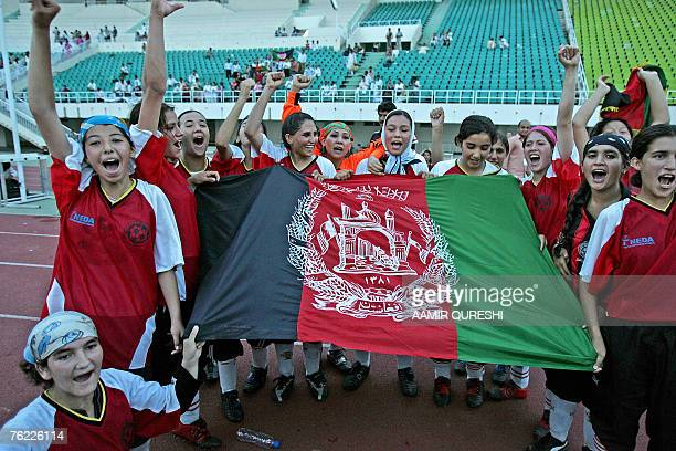 Afghanistan's women football team players carry their national flag as they celebrate after defeating Pakistan's Baluchistan National Women football...