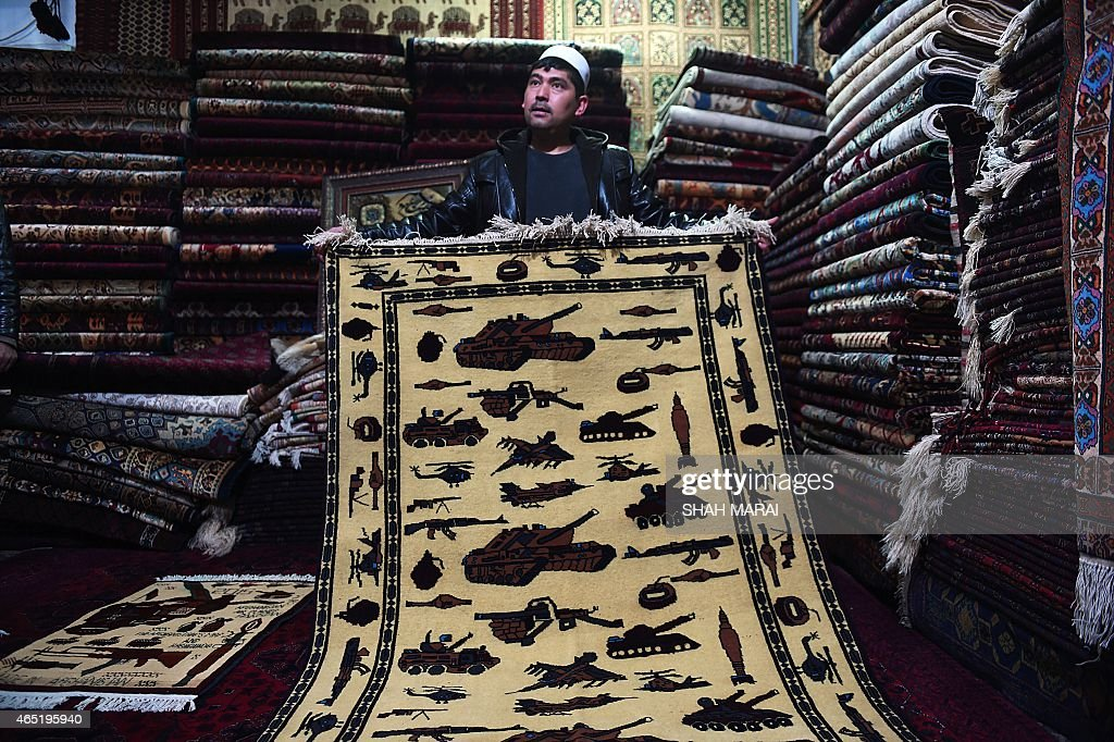 Afghanistan-unrest-carpets,FEATURE by Emal Haidary In this photo taken on February 2, 2015, an Afghan carpet trader displays a carpet showing different weapons and machinery as he waits for customers at his shop on Chicken Street in Kabul. More than three decades of war have damaged Afghanistan's once-thriving carpet industry, but weavers are tapping into the bloody past to boost their fortunes with 'war rugs' depicting guns, tanks and warplanes. AFP PHOTO / SHAH Marai