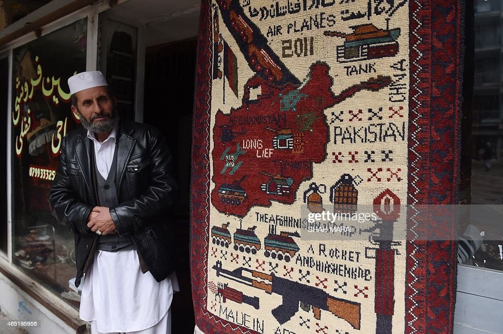 Afghanistan-unrest-carpets,FEATURE by Emal Haidary In this photo taken on February 2, 2015, an Afghan carpet trader looks at a carpet showing a map of Afghanistan with different weapons displayed, as he waits for customers in his shop on Chicken Street in Kabul. More than three decades of war have damaged Afghanistan's once-thriving carpet industry, but weavers are tapping into the bloody past to boost their fortunes with 'war rugs' depicting guns, tanks and warplanes. AFP PHOTO / SHAH Marai