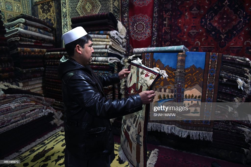 Afghanistan-unrest-carpets,FEATURE by Emal Haidary In this photo taken on February 2, 2015, an Afghan carpet trader displays a carpet showing the map of Afghanistan and flags of different countries as he waits for customers in his shop on Chicken Street in Kabul. More than three decades of war have damaged Afghanistan's once-thriving carpet industry, but weavers are tapping into the bloody past to boost their fortunes with 'war rugs' depicting guns, tanks and warplanes. AFP PHOTO / SHAH Marai