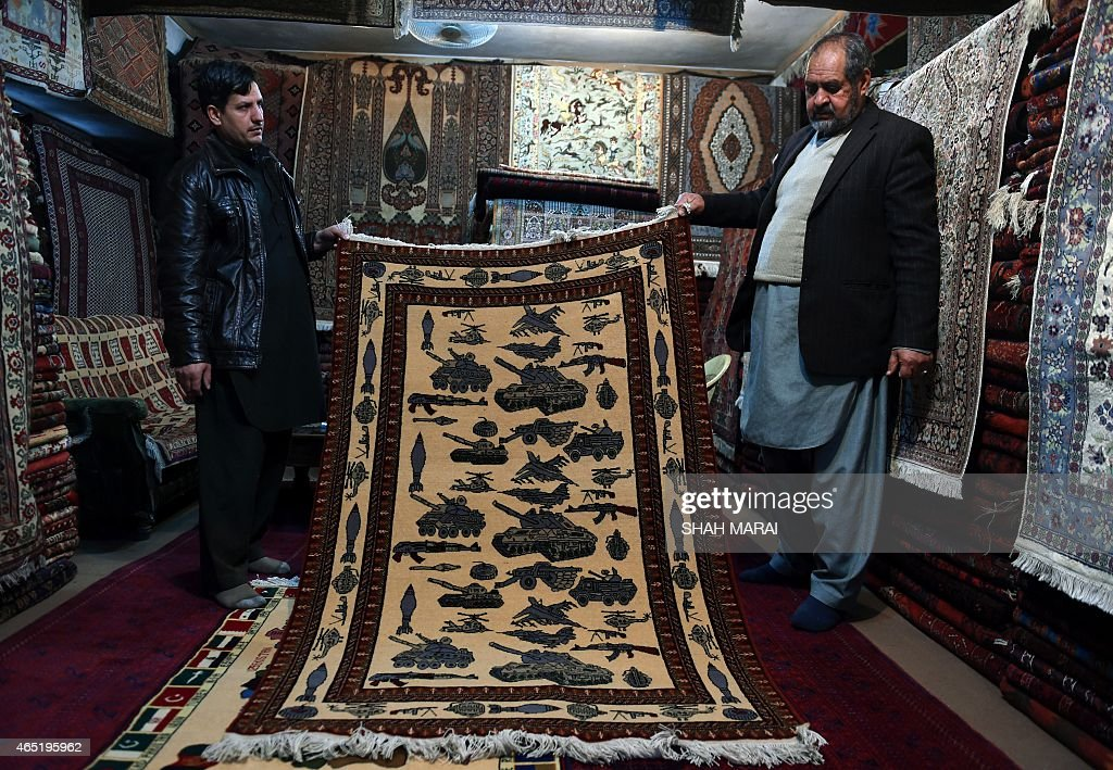 Afghanistan-unrest-carpets,FEATURE by Emal HaidaryIn this photo taken on February 2, 2015, an Afghan carpet trader displays a carpet showing different weapons and machinery as he waits for customers at his shop on Chicken Street in Kabul. More than three decades of war have damaged Afghanistan's once-thriving carpet industry, but weavers are tapping into the bloody past to boost their fortunes with 'war rugs' depicting guns, tanks and warplanes. AFP PHOTO / SHAH Marai
