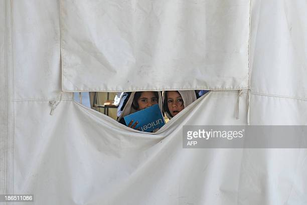 AfghanistanunresteducationchildrenFEATURE by Ben Sheppard In this picture taken on September 25 schoolgirls look out from their classroon in a tent...