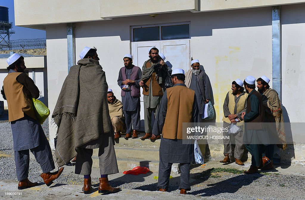 Afghanistan-unrest-prison,FOCUS by Ben Sheppard In this picture taken on January 4 ,2013, released Taliban prisoners stand in the sun after a ceremony in Pul-e-Charkhi jail. With tears streaming down their faces, scores of suspected Afghan militants embraced waiting relatives and walked to freedom -- just one sign of increasing attempts at reconciliation after 11 years of war. About 80 men, all wearing white skull caps, were released from jail on January 4, 2013, at a ceremony inside Pul-e-Charkhi, Afghanistan's largest prison located on dusty flatlands east of the capital Kabul. AFP PHOTO/ Massoud HOSSAINI