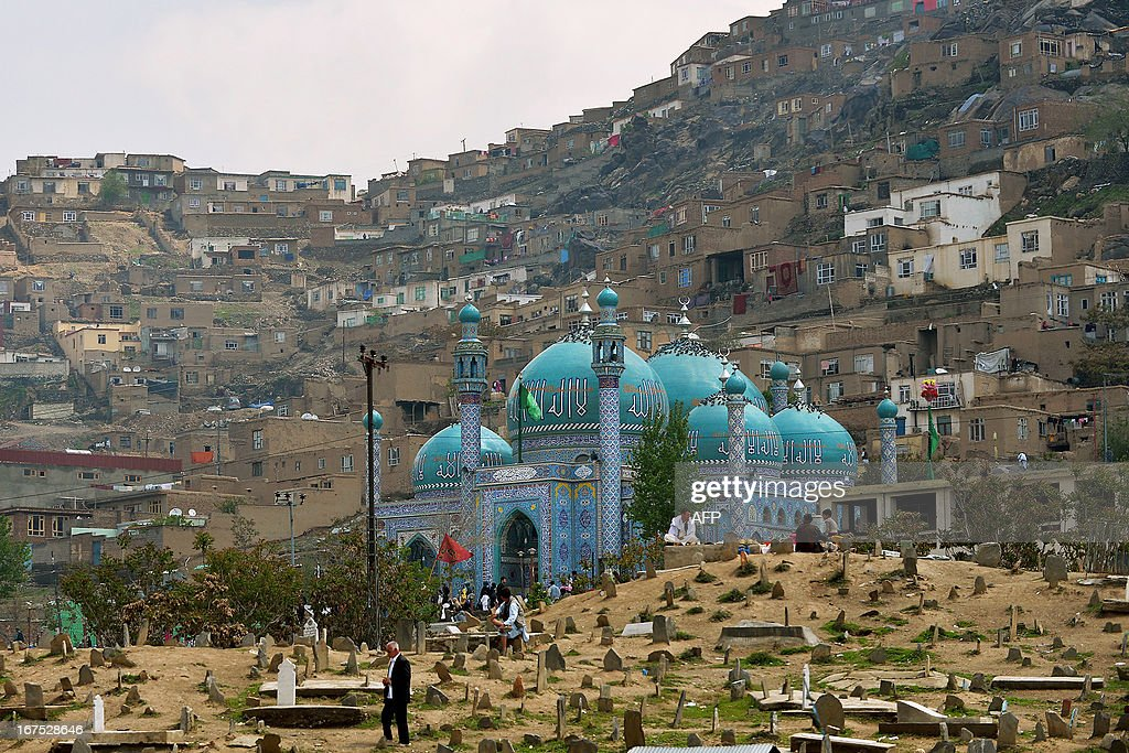 Afghans are pictured at the Karte Sakhi cemetary on the foot of Karte Sakhi's Shrine in the foothills of TV Mountain in Kabul on April 26, 2013. The shrine is the second most sacred place of Shia worship in Afghanistan. AFP PHOTO/Manjunath KIRAN