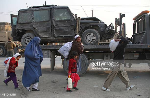 Afghans walk near a damaged car following a suicide car bomb attack on a European Union police vehicle along the KabulJalalabad road in Kabul...