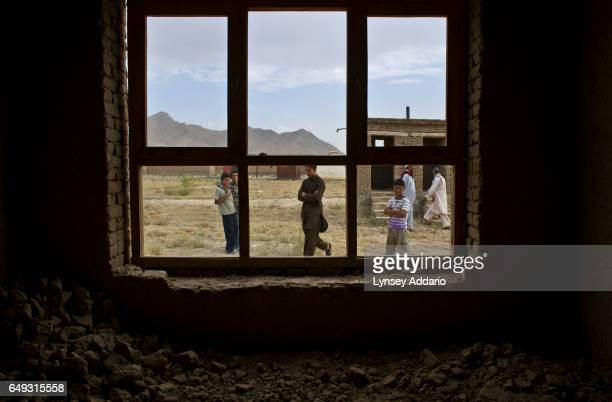 Afghans walk through the mostly abandoned land allocation settlement of AliceGhan about 30 miles outside of Kabul Afghanistan July 22 2011