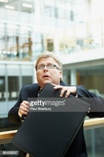 Afraid businessman holding briefcase : Stock Photo