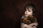 Child abuse theme - scared child with teddy bear