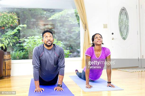 Africam American heterosexual couple doing yoga together