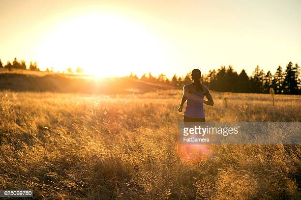African American adult female athlete trail running through tall grass