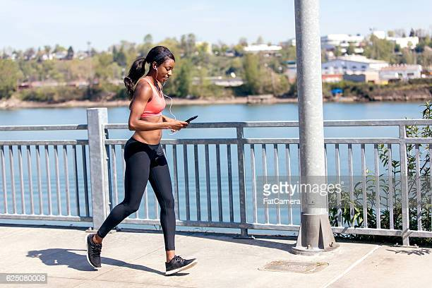 African American adult female listening to music and jogging