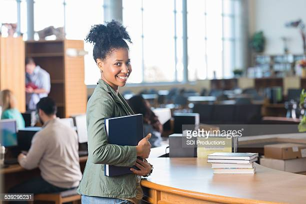 African American adult woman checking out books at college library