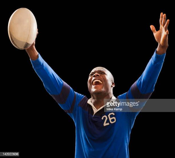 African American athlete holding rugby ball