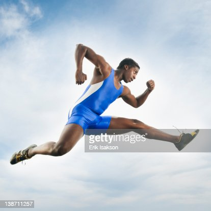 African American athlete jumping in mid-air : Stock Photo