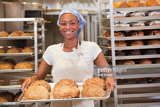 African American baker holding tray of bread in bakery