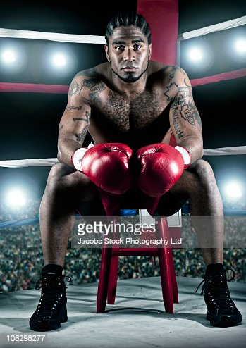 African American boxer sitting in boxing ring : Stock-Foto