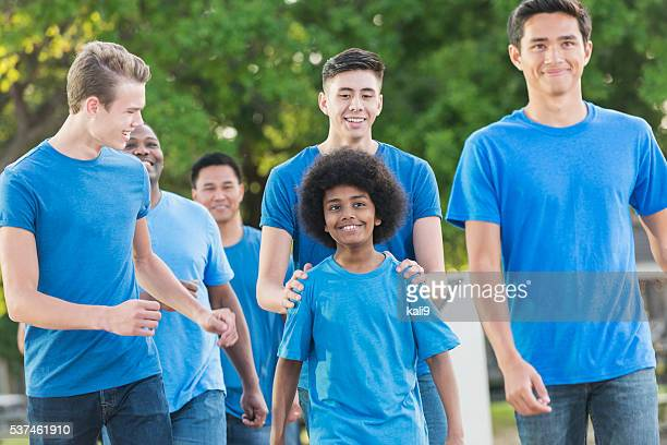 African American boy and group of teens in blue shirts