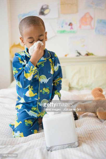 African American boy blowing his nose on bed