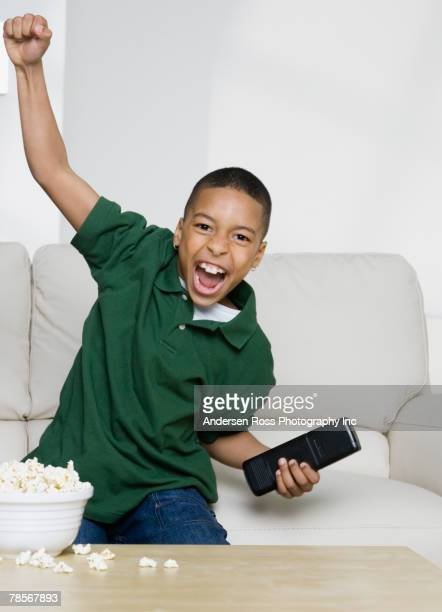 African American boy cheering on sofa