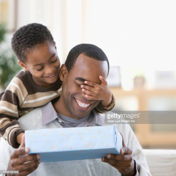 African American boy covering father's eyes and giving him a gift