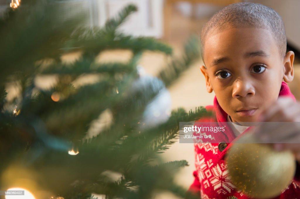 African American boy decorating Christmas tree : Stock Photo