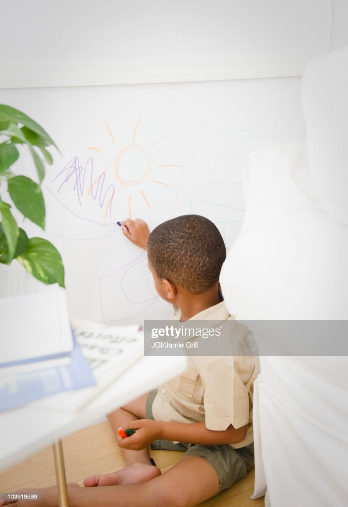 African American boy drawing on wall with crayon : Stock Photo