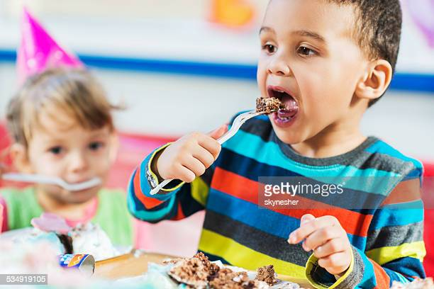 African American boy eating birthday cake.