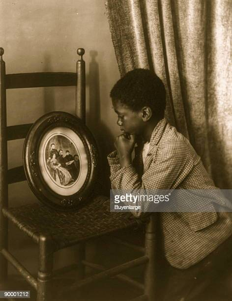 African American boy elbows resting on chair looking at picture of Abraham Lincoln and family in oval frame which rests on chair