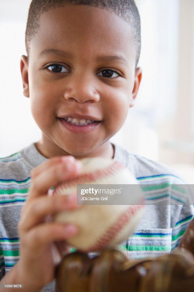 African American boy holding baseball and baseball glove