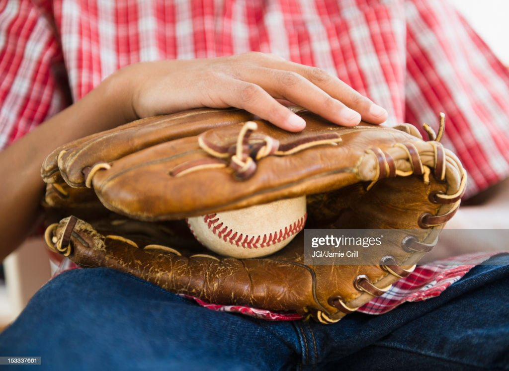 African American boy holding baseball and glove