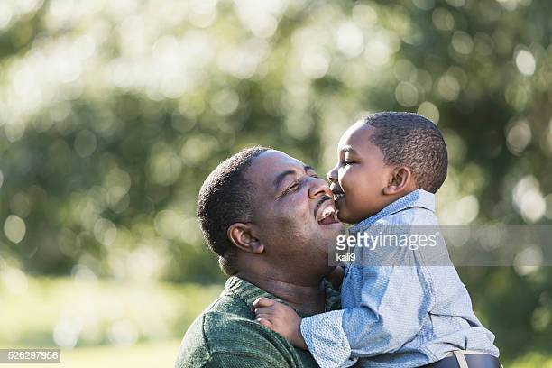 African American boy kissing father on cheek