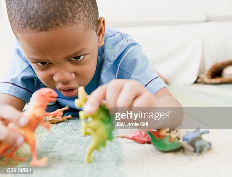 African American boy laying on floor playing with toy dinosaurs : Stock Photo